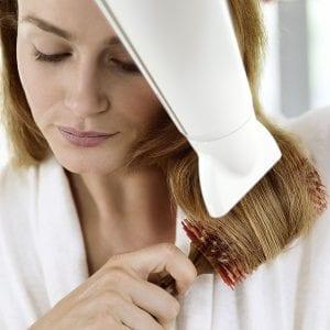 Frau mit kabellosem Haartrockner